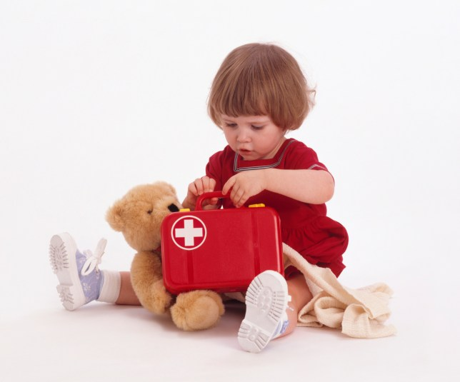 Toddler with toy first aid kit and teddy
