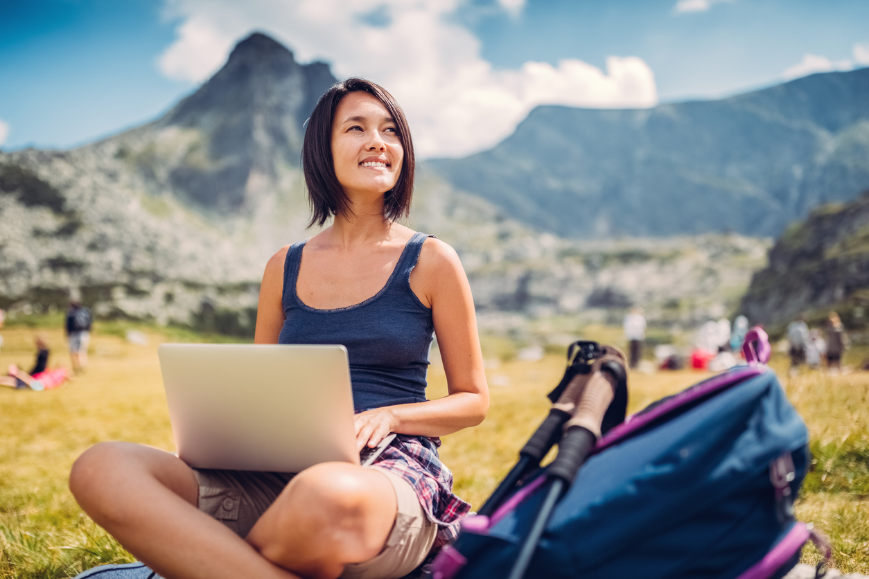 Hiker with laptop sitting on the ground