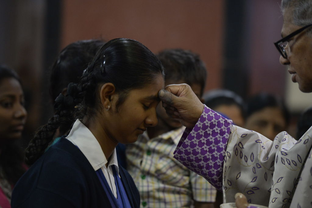a young girl gets a cross drawn on her forehead by a priest for ash wednesday