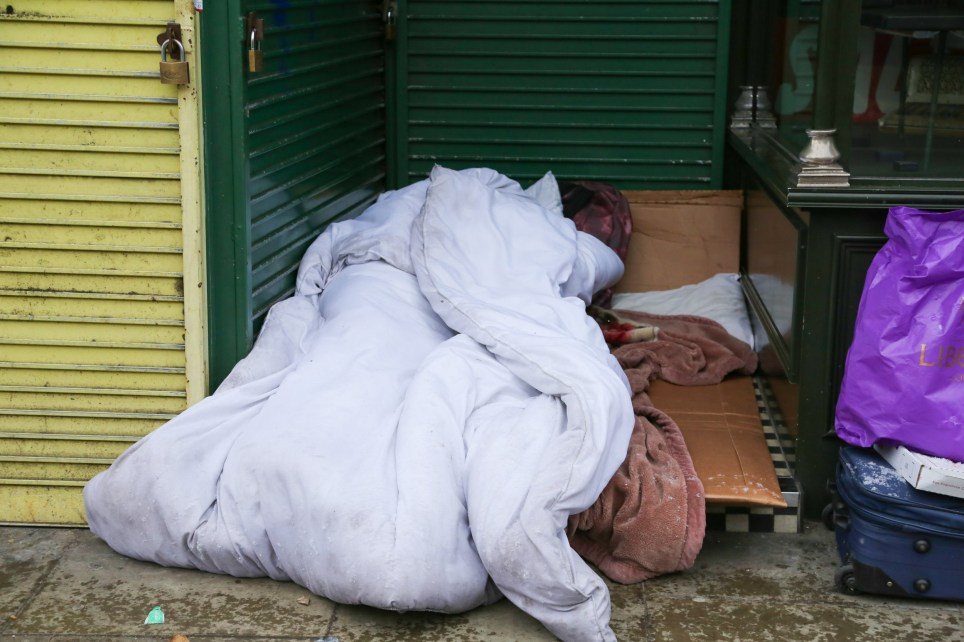 """A person sleeping in a sleeping bag in-between shops in Green Lanes in London Borough of Haringey, north London as snow starts to fall in London, before the arrival of """"The Beast from the East"""", which is expected to see temperatures plummet to -15c and bring heavy snow falls. Featuring: Atmosphere, View Where: London, United Kingdom When: 26 Feb 2018 Credit: WENN"""
