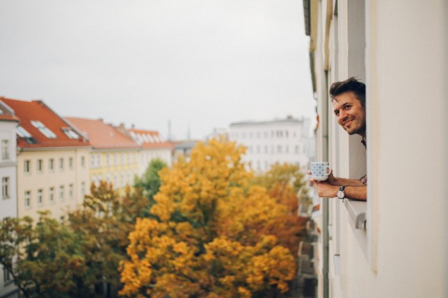 A young man is drinking coffee and looking from an apartment window, enjoying the afternoon on a cloudy Autumn day in Berlin, Prenzlauer Berg.