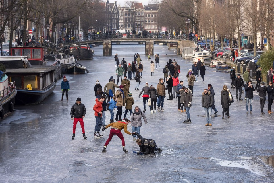 epa06575172 People skate on the ice of the frozen canal 'Prinsengracht' in Amsterdam, Netherlands, 02 March 2018. EPA/EVERT ELSINGA