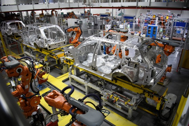 "SOLIHULL, ENGLAND - MARCH 06: Robotic systems work on the chassis of a car during an automated stage of production at the Jaguar Land Rover factory on March 1, 2017 in Solihull, England. The company has pledged it's 'heart and soul' to production in the UK after producing the new ""Velar"" model for global sale, at their Solihull factory. (Photo by Leon Neal/Getty Images)"