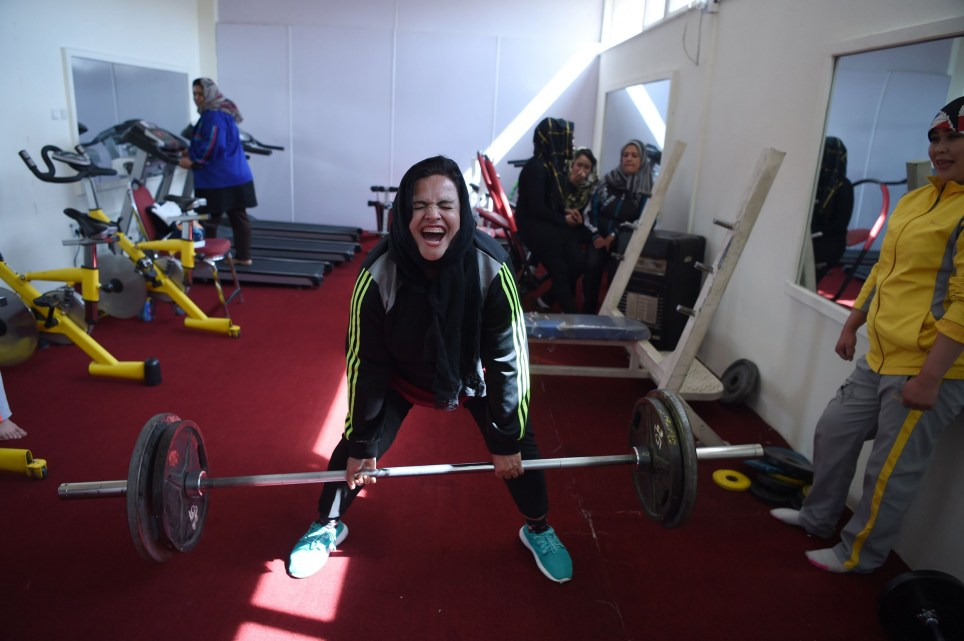In this Photo taken on March 4, 2018, Afghanistan national powerlifting team member Rasheda Parhiz, 40, reacts during a deadlift exercise as teammate Sadya Ayubi looks on during a training session at a women's gym at Ghazi stadium in Kabul. Inside the Afghanistan Powerlifting Federation's cramped gym, Rasheda Parhiz lays on a bench wearing a tunic over sweatpants and holding a 70-kilogramme weighted bar above her scarf-covered head. The 40-year-old began powerlifting several years ago to help lose weight -- she used to weigh 120kg and hid her ample body under a burqa. / AFP PHOTO / WAKIL KOHSAR / TO GO WITH: AFGHANISTAN-WEIGHTLIFTING-WOMEN, FOCUS by Anne CHAONWAKIL KOHSAR/AFP/Getty Images