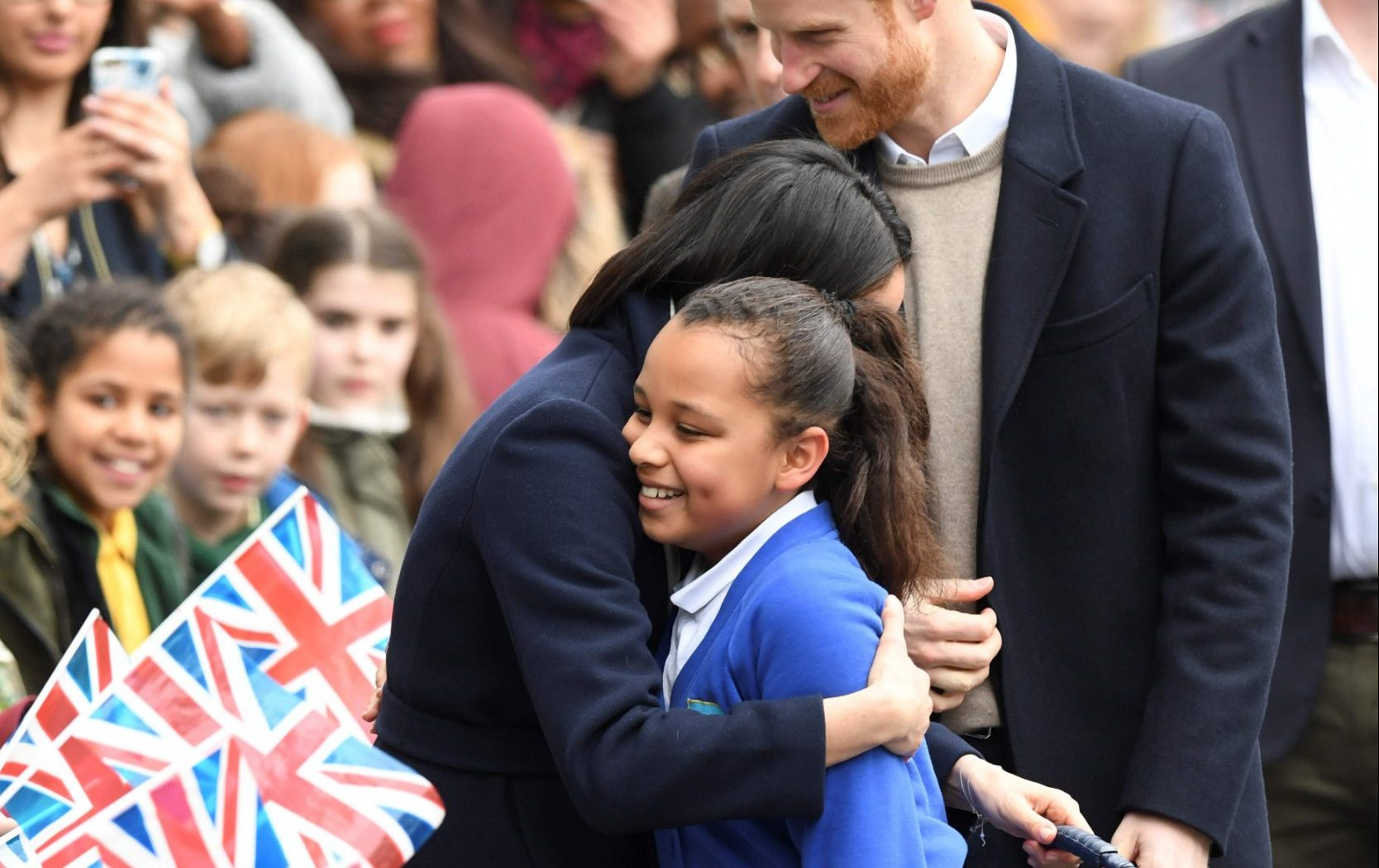 Britain's Prince Harry (C) and his fiancee US actress Meghan Markle (L) greet well-wishers as they arrive at Millennium Point to attend an event hosted by by social enterprise Stemettes to celebrate International Women's Day in Birmingham on March 8, 2018. Prince Harry and Meghan Markle visited Birmingham to learn more about the work of two projects which support young people from the local community. The event at Millennium Point aims to inspire the next generation of young women to pursue careers in Science, Technology, Engineering and Maths (STEM). / AFP PHOTO / Paul ELLISPAUL ELLIS/AFP/Getty Images