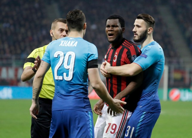 AC Milan's Franck Kessie, second from right, discusses with Arsenal's Granit Xhaka during the Europa League round of 16 first-leg soccer match between AC Milan and Arsenal, at the Milan San Siro Stadium, Italy, Thursday, March 8, 2018. (AP Photo/Luca Bruno)