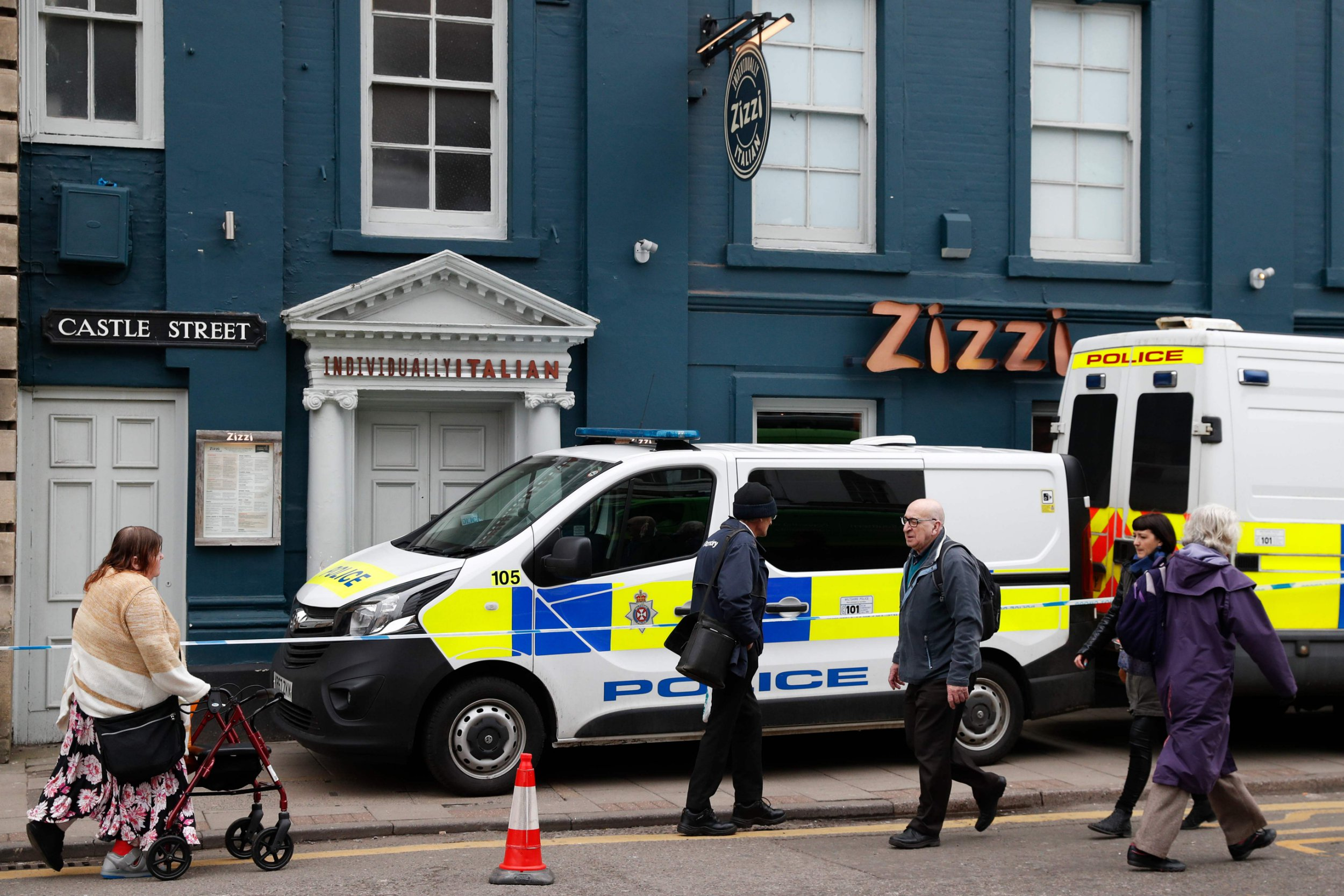 """Pedestrians walk past a cordoned-off branch of the Italian chain restaurant Zizzi close to The Maltings shopping centre in Salisbury, southern England, on March 8, 2018 which was closed in connection to the ongoing major incident sparked after a man and a woman were found critically ill on a bench at the shopping centre on March 4 after being apparently poisoned with what was later identified as a nerve agent sparking a major incident. Britain vowed on March 8 to act """"without hesitation"""" if a state is found responsible for a nerve agent attack on a former Russian double agent, as police said 21 people in total had received medical treatment following the incident. Sergei Skripal and his daughter Yulia remain unconscious in a critical but stable condition following the attack on Sunday in the sleepy south-western English city of Salisbury. / AFP PHOTO / Adrian DENNISADRIAN DENNIS/AFP/Getty Images"""