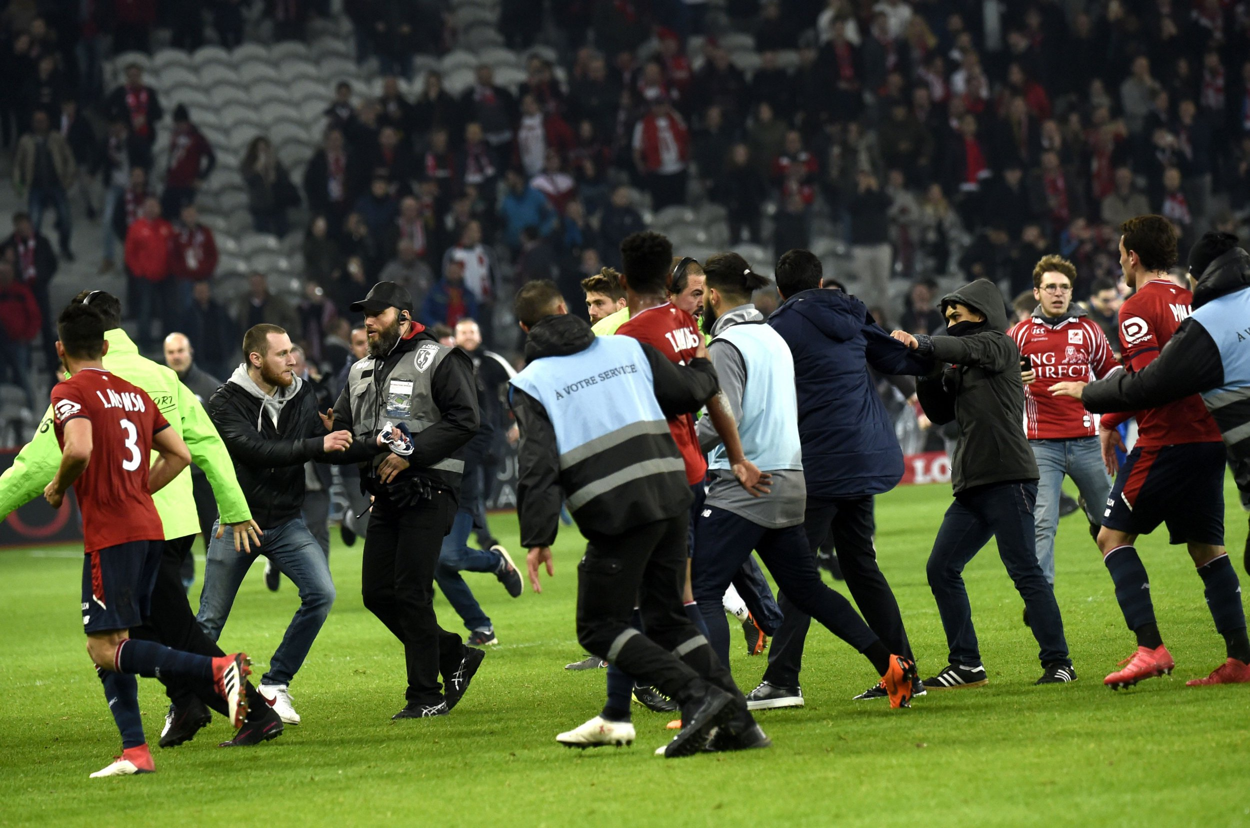 Lille' supporters invade the pitch at the end of the French L1 football match between Lille and Montpellier on March 10, 2018 at the Pierre Mauroy stadium in Lille, northern France. / AFP PHOTO / FRANCOIS LO PRESTIFRANCOIS LO PRESTI/AFP/Getty Images