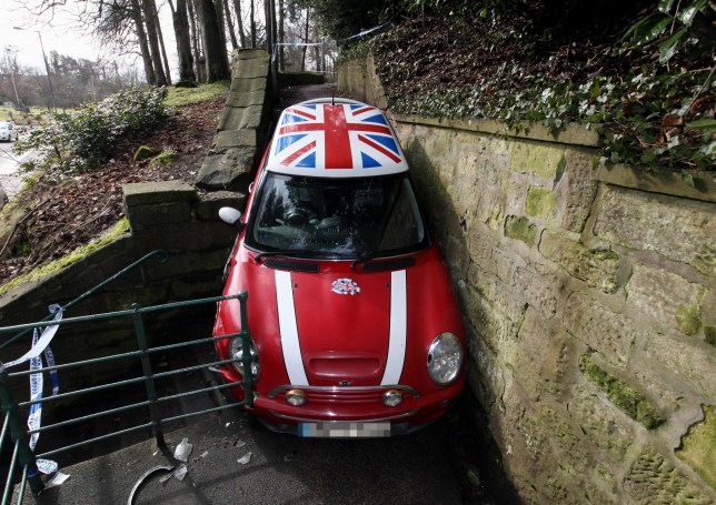 PIC BY DAVID CHARLTON PHOTOGRAPHY / CATERS NEWS - (PICTURED The car stuck halfway down the stairs) - A suspected car thief tried to make his getaway in this iconic Mini Cooper - only to get wedged on the stairs and had to be rescued by police. In a bid to copy a scene from the Italian Job, the 31 year old man risked driving down the winding public stairs at 11.30pm. But halfway down the stone steps the car became trapped and he couldnt even open the doors in Morpeth, Northumberland. Emergency services were called and he had to be helped out of the 16 year old Mini Cooper where he was then arrested for aggravated vehicle taking. SEE CATERS COPY