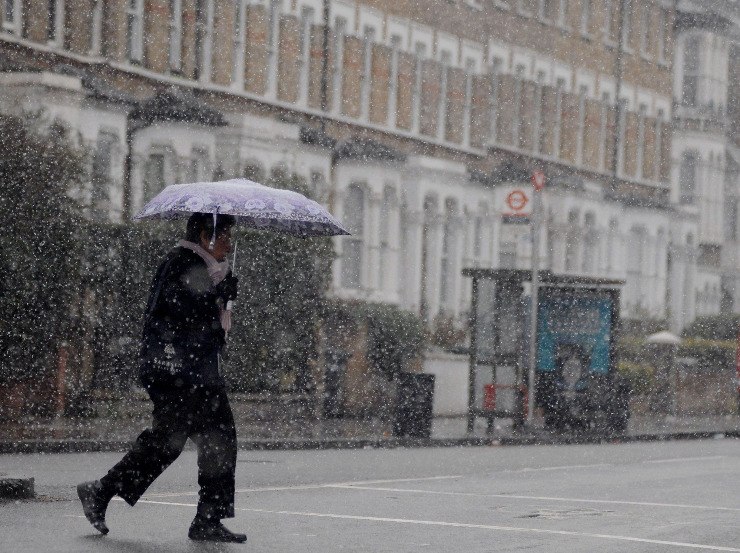 Mandatory Credit: Photo by Gill Allen/REX/Shutterstock (9469231b) A woman sheltering from the snow under an umbrella crosses the road near Stockwell in south London in the United Kingdom's capital, 17th March 2018. Snow and ice has hit parts of the United Kingdom as a cold snap dubbed the mini 'beast from the east' sweeps in with yellow 'be aware' warnings in place in parts of the country till Sunday and cancelled flights. Seasonal weather, London, UK - 17 Mar 2018
