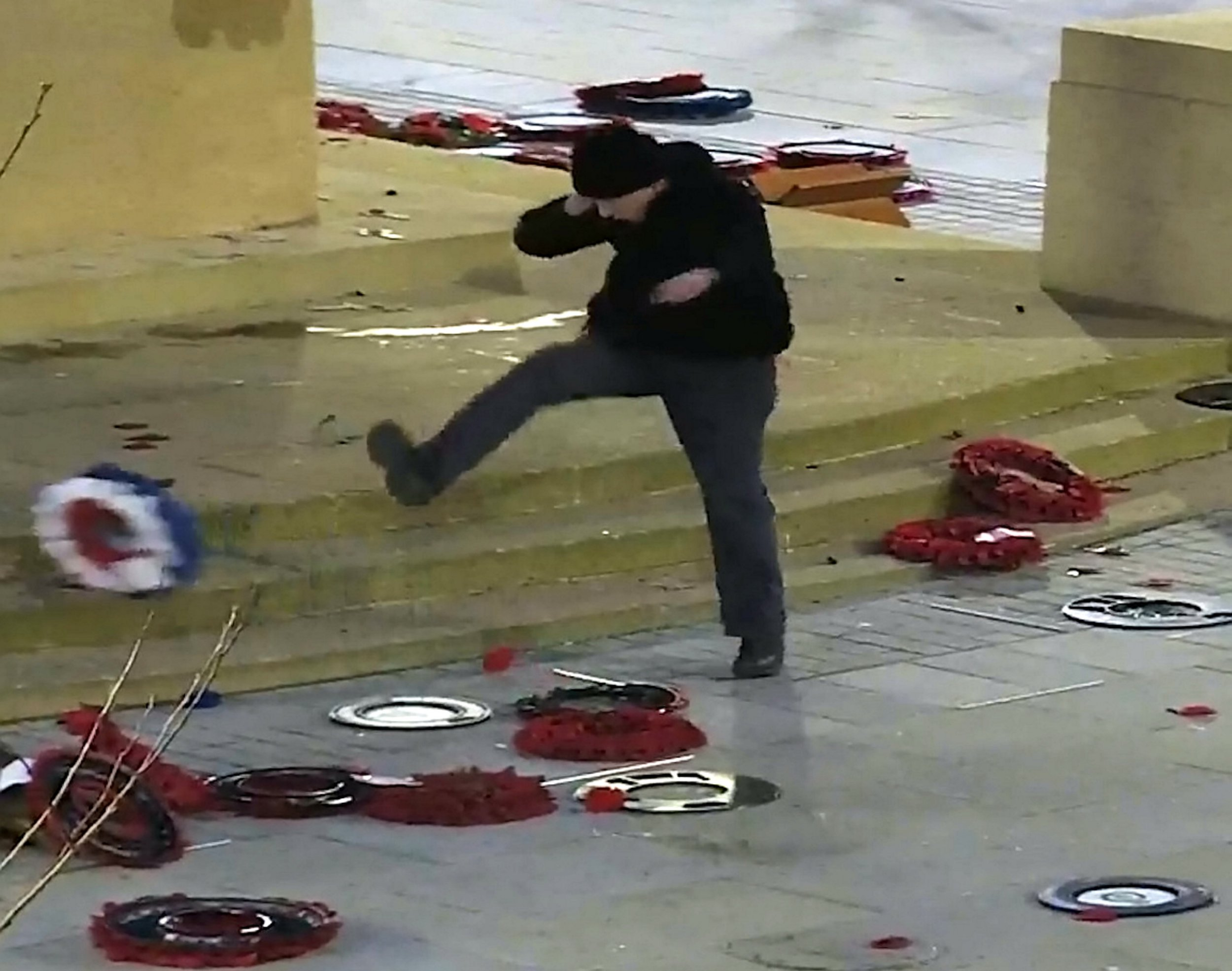 """Video grab of the moment a former serviceman was caught on CCTV kicking poppy wreaths off a Cenotaph memorial. See SWNS story SWCENOTAPH; Peter Lear, 49, was filmed for 10 minutes as he systematically kicked the wreaths around the ground in the early hours of the morning. He suffers from PTSD and could be heard muttering about """"Home Office corruption"""" during his appearance before Bristol Magistrates Court. Lear, of Knowle, Bristol, admitted a charge of criminal damage."""
