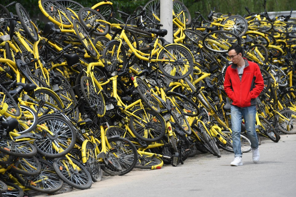 A man walks past shared bikes placed at a repair factory in Beijing, China