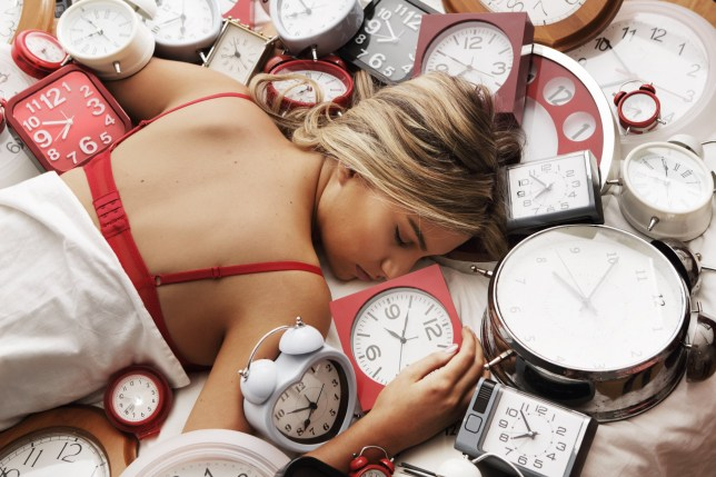 Woman asleep surrounded by lots of clocks
