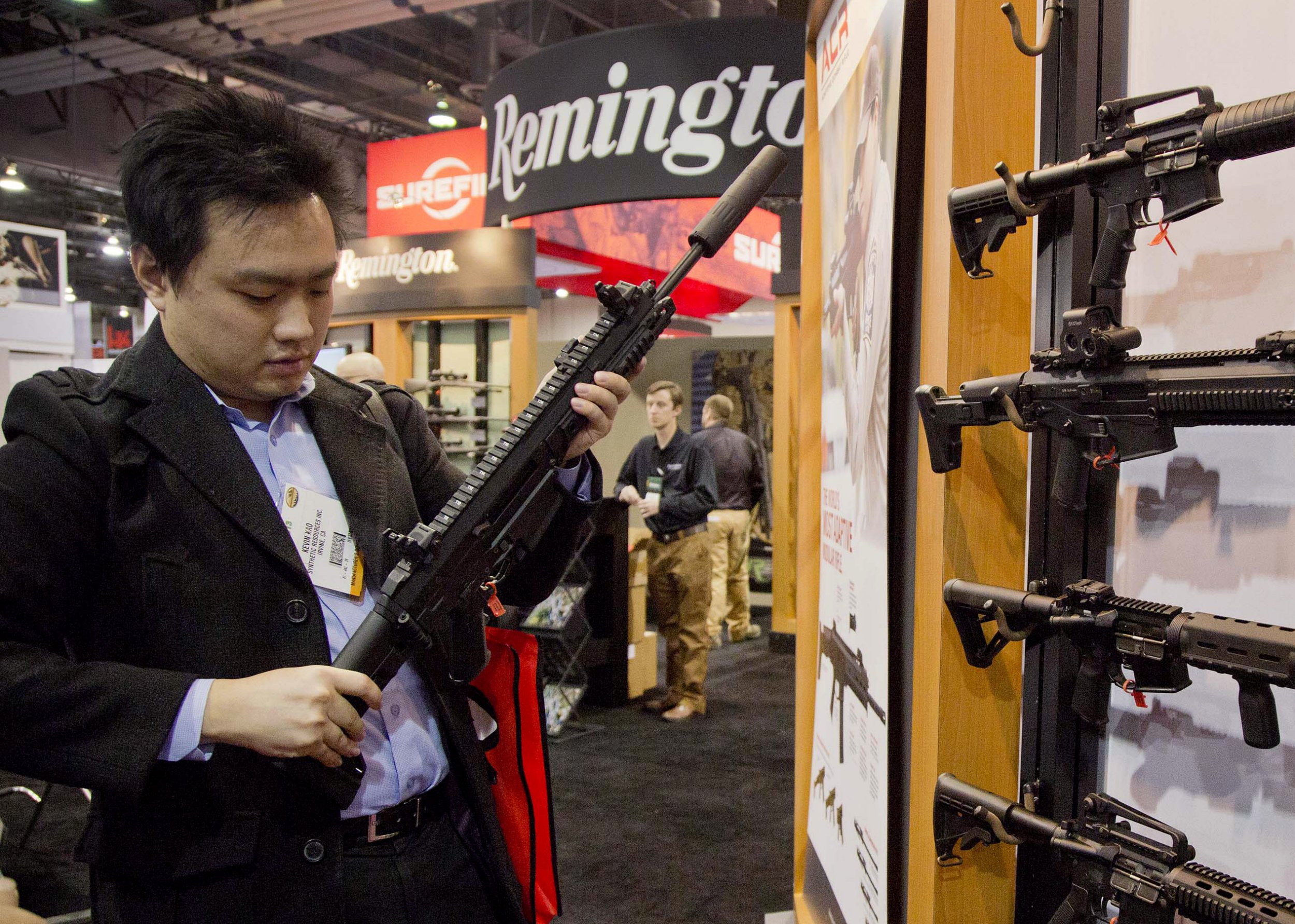 FILE- In this Jan. 15, 2013, file photo, accessories manufacturer Kevin Kao, of Irvine, Calif., examines a military grade Remington Adaptive Combat Rifle at the 35th annual SHOT Show in Las Vegas. U.S. gun maker Remington Outdoor Company filed for bankruptcy protection, after years of falling sales and lawsuits tied to the Sandy Hook Elementary School massacre. Records from the bankruptcy court of the district of Delaware show that the company filed late Sunday, March 25, 2018. (AP Photo/Julie Jacobson, File)