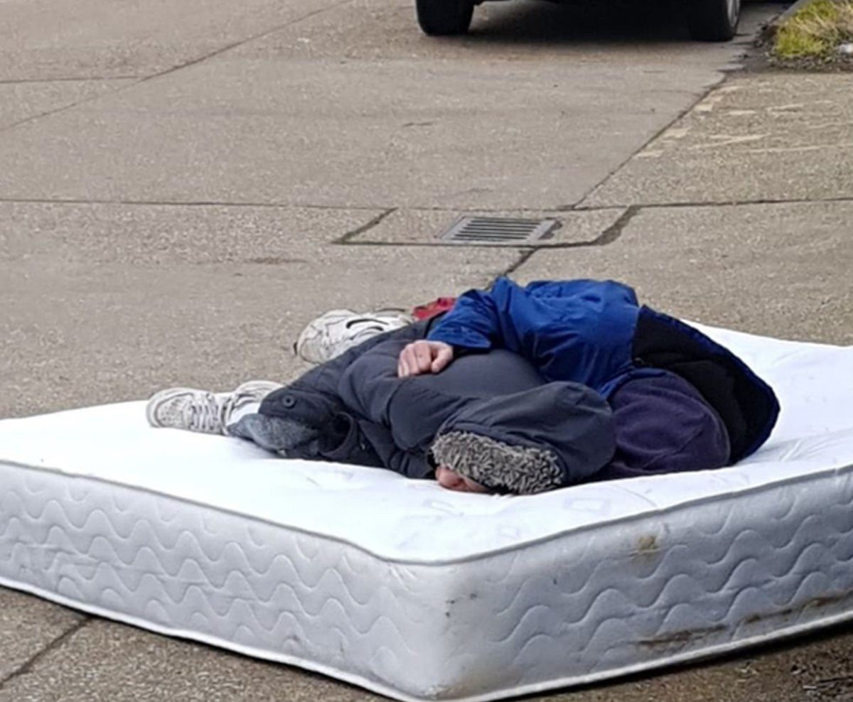 A heartbreaking photograph of a homeless couple has sparked a mixed reaction from residents. The picture shows two people asleep on a dirty mattress in the middle of a residential road in South Ockendon, Essex.