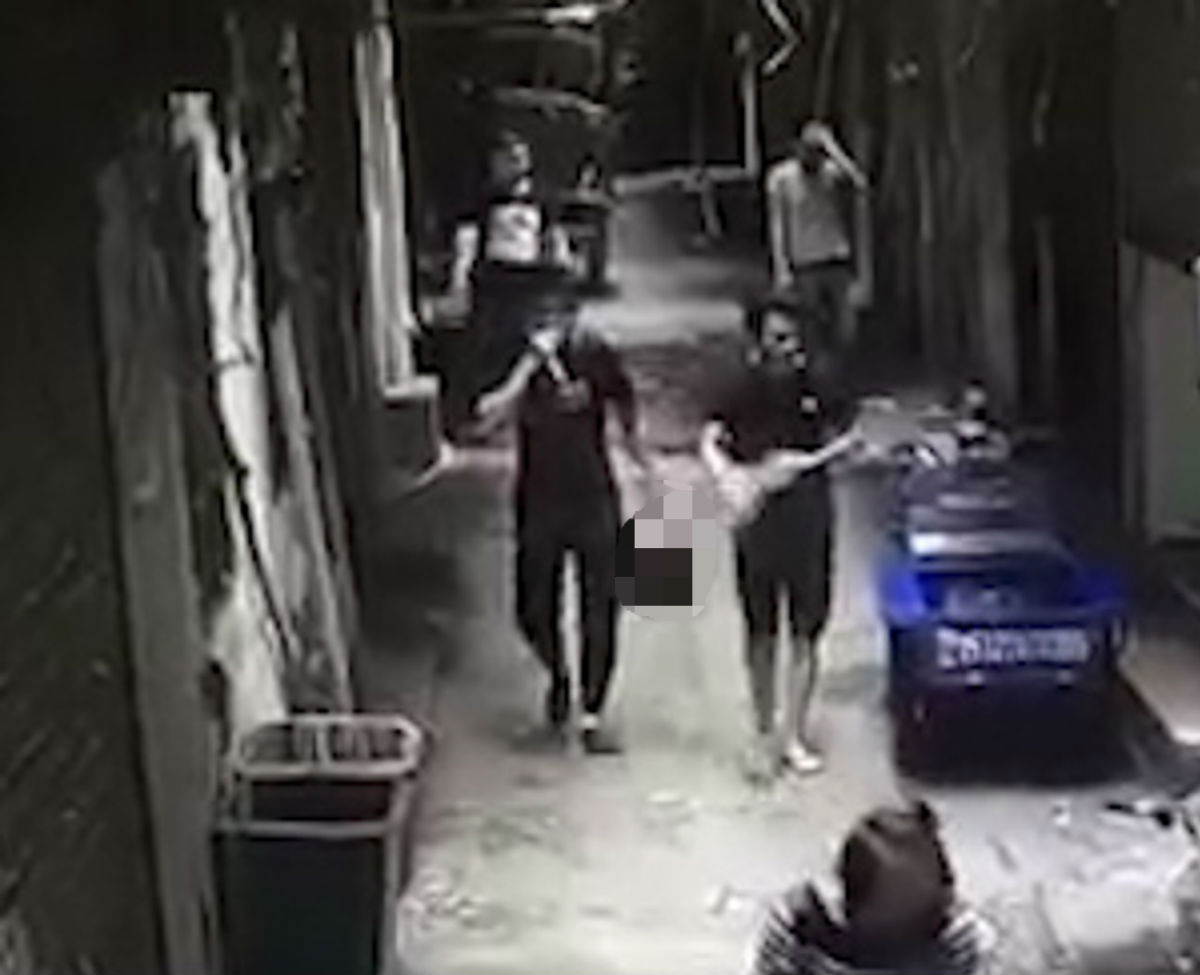 Man walks calmly through alley holding wife's decapitated head