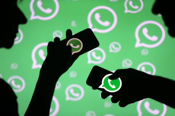 Men pose with smartphones in front of displayed Whatsapp logo in this illustration September 14, 2017. REUTERS/Dado Ruvic - RC1754A449A0