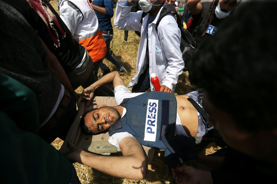 Mortally wounded Palestinian journalist Yasser Murtaja, 31, is evacuated during clashes with Israeli troops at the Israel-Gaza border, in the southern Gaza Strip April 6, 2018. Picture taken April 6, 2018. REUTERS/Ibraheem Abu Mustafa