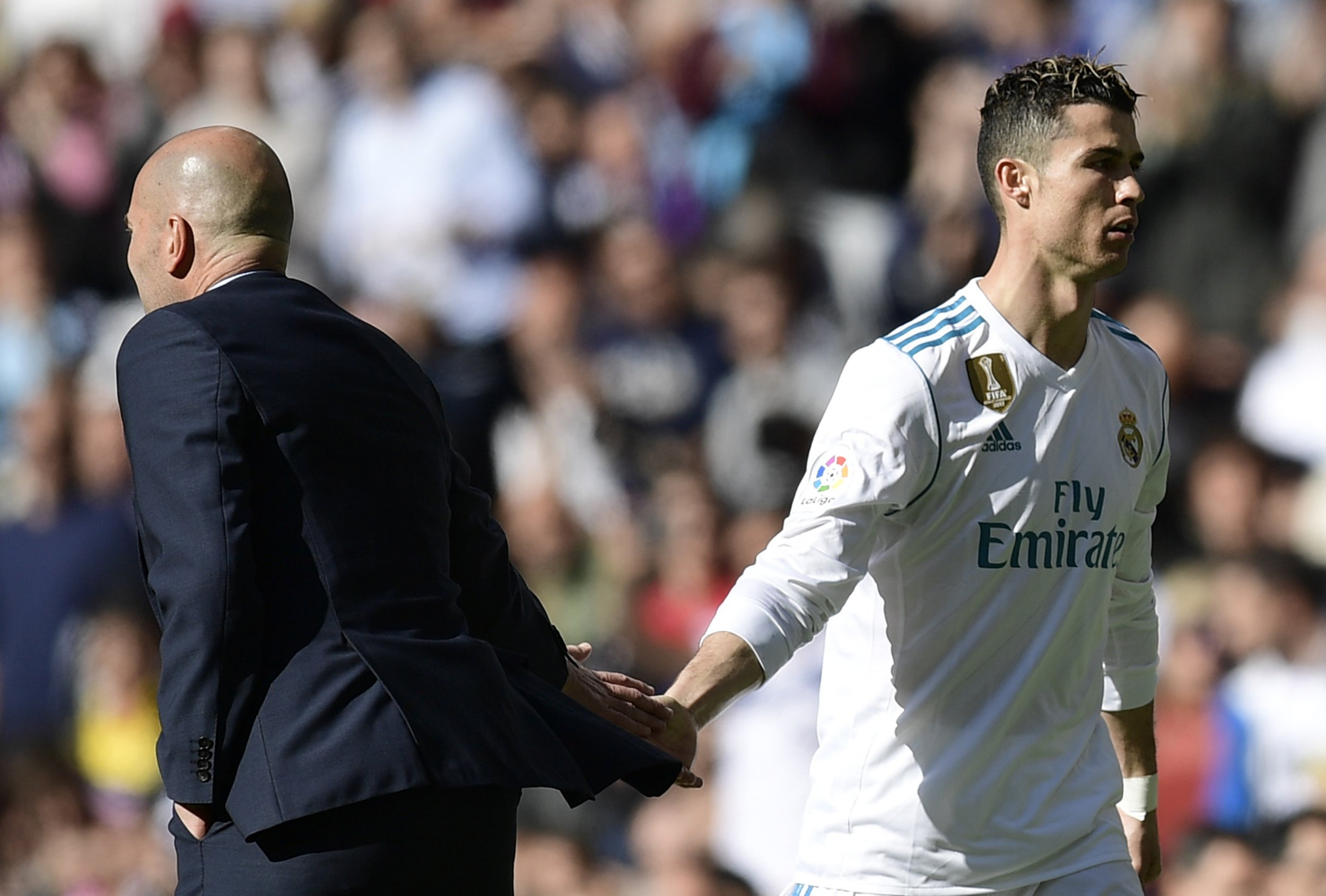 Real Madrid's French coach Zinedine Zidane (L) cheers Real Madrid's Portuguese forward Cristiano Ronaldo as he leaves the field during the Spanish league football match between Real Madrid CF and Club Atletico de Madrid at the Santiago Bernabeu stadium in Madrid on April 8, 2018. / AFP PHOTO / JAVIER SORIANOJAVIER SORIANO/AFP/Getty Images