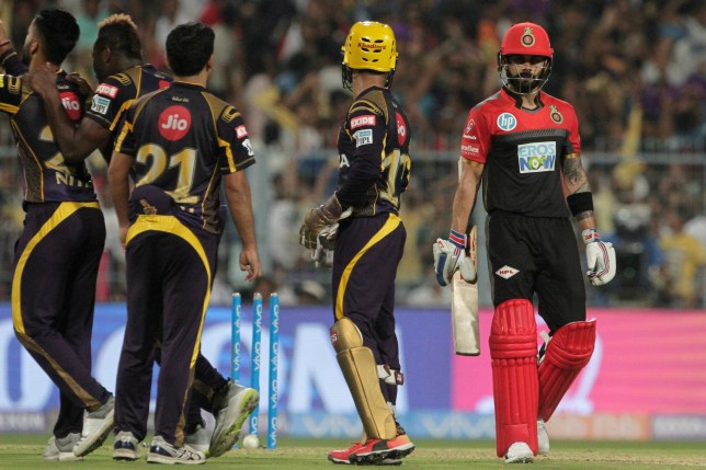 Royal Challengers Bangalore's Virat Kohli walks out as Kolkata Knight Riders' players celebrate his dismissal during VIVO IPL cricket T20 match in Kolkata, India, Sunday, April 8, 2018. (AP Photo/Bikas Das)