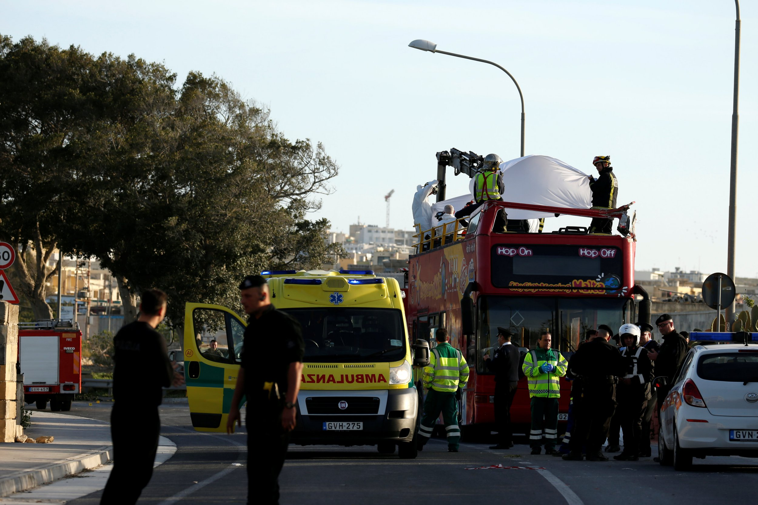 Rescue workers retrieve a body from the top of an open top, double-decker sightseeing bus after it crashed into some low-lying tree branches, in Zurrieq, Malta April 9,2018. REUTERS/Darrin Zammit Lupi