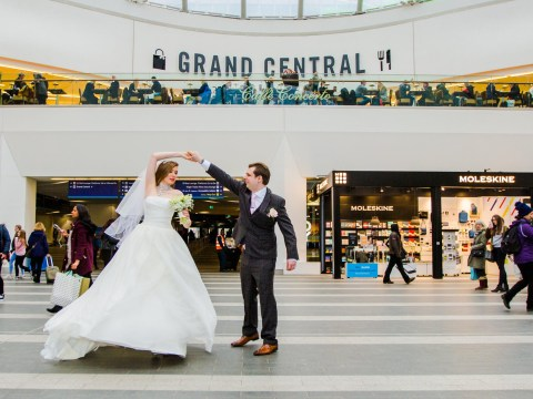 Couple pose for wedding photos in New Street train station