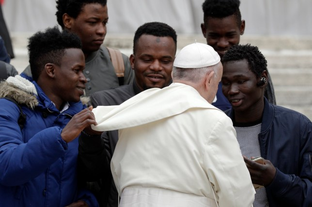 """A migrant pulls on Pope Francis' cape as the pontiff meets a group of migrants taking part in a project on social integration organized by the charity """"Agata Smeralda"""", during his weekly general audience, in St.Peter's Square at the Vatican, Wednesday, April 11, 2018. (AP Photo/Andrew Medichini)"""