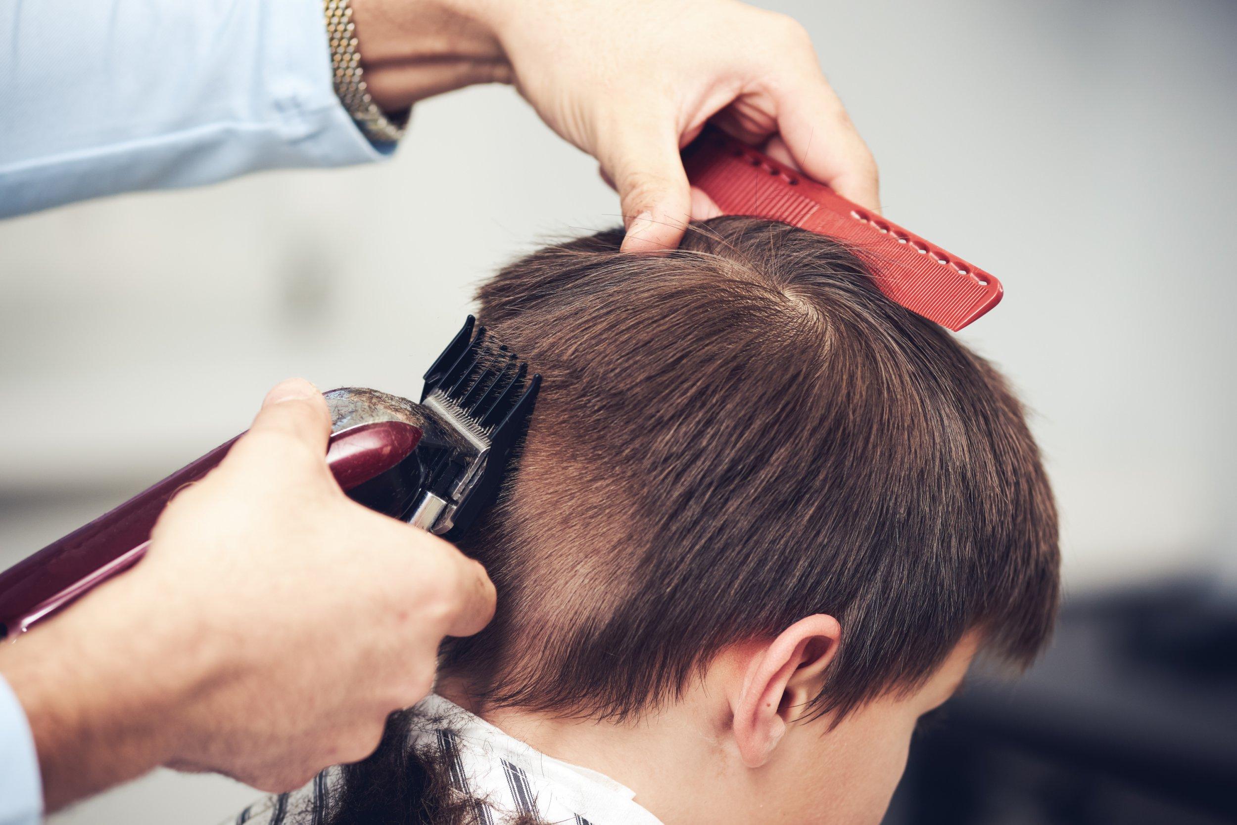 European boy getting haircut in barbershop.; Shutterstock ID 1013521075; Purchase Order: -