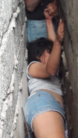 NEWS COPY - WITH PICTURES This is the bizarre moment a drunk woman had to be rescued - after climbing on a roof and falling down between two houses. The intoxicated resident had been drinking with friends returned home on January 27 and decided to climb on to the roof of her home in Laguna, Philippines. But she slipped and tumbled into the gap between the two homes made from breeze blocks. Neighbours heard her cries from help and alerted rescuers who spent six hours trying to free her from the uncomfortable position. The Bureau of Fire Protection (BFP) said that initially the woman had resisted being rescued due to her drunken state. A spokesman said: ''It took six hours to rescue her. In the end, the rescuers had to make a hole in the wall to remove her. ''She sustained scratches and some bruises after the incident. Her friends asked that her identity was not revealed.'' ENDS
