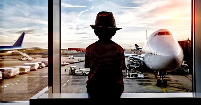 Deutschland, Frankfurt am Main, Flughafen, Junge schaut aus dem Fenster, Reise, Urlaub, Fernweh, Kind, Tourist