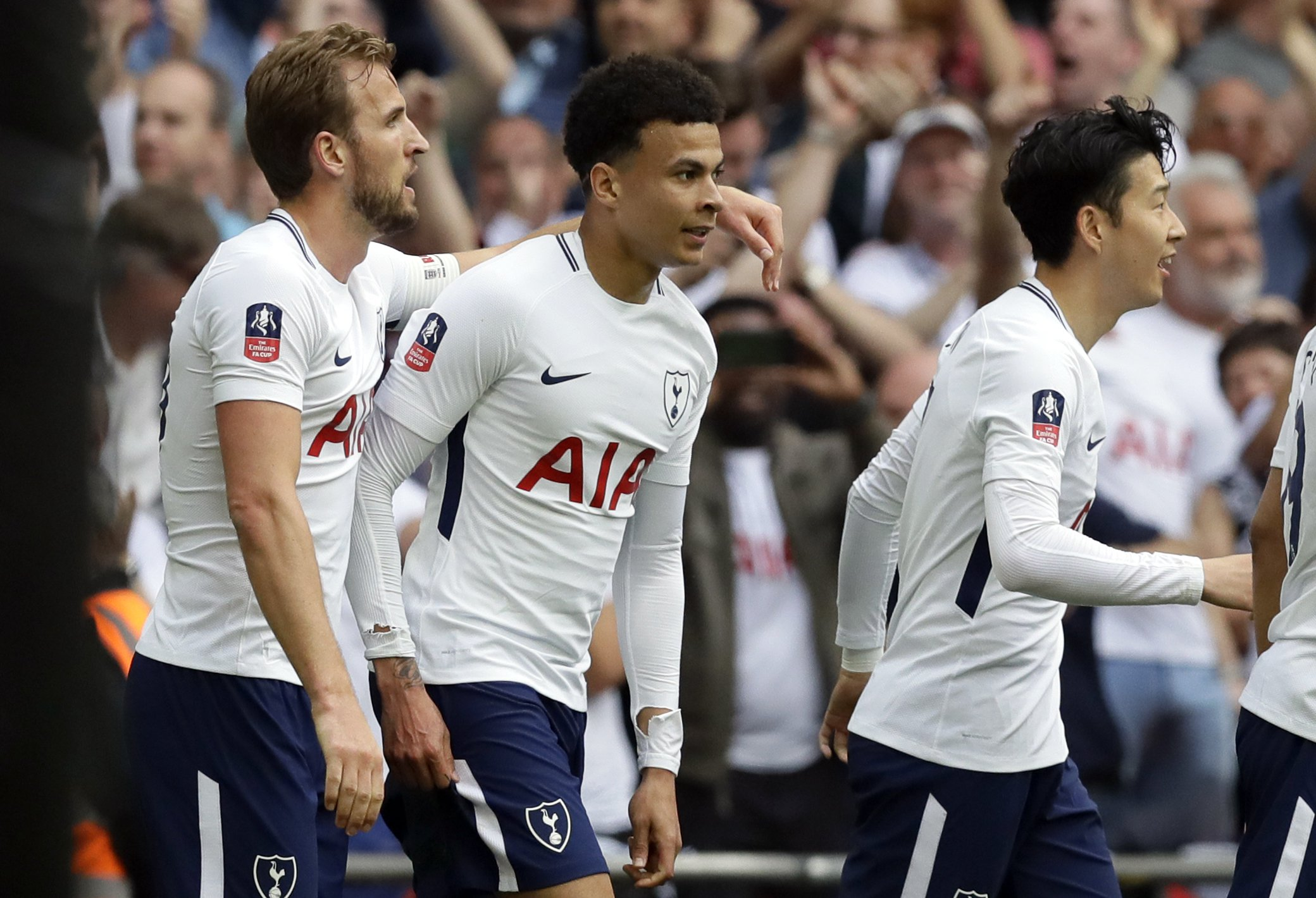 Tottenham's Dele Alli, center, celebrates with Harry Kane, left, and Son Heung-min after scoring the opening goal during the English FA Cup semifinal soccer match between Manchester United and Tottenham Hotspur at Wembley stadium in London, Saturday, April 21, 2018. (AP Photo/Kirsty Wigglesworth)