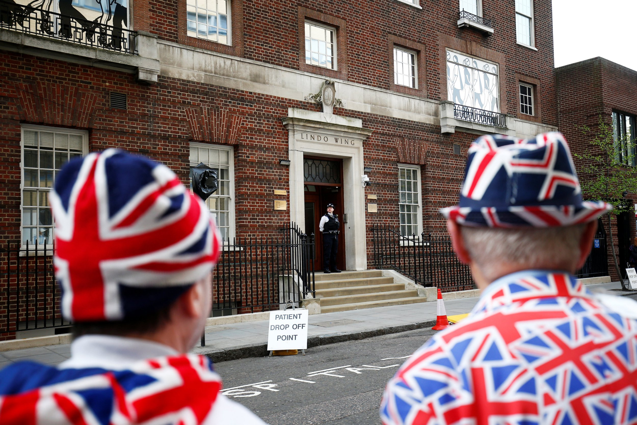 Supporters of the royal family stand outside the Lindo Wing of St Mary's Hospital after Britain's Catherine, the Duchess of Cambridge, was admitted after going into labour ahead of the birth of her third child, in London, April 23, 2018. REUTERS/Henry Nicholls