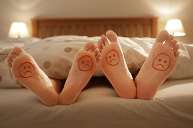 Couple in bed with happy and unhappy faces drawn on their feet