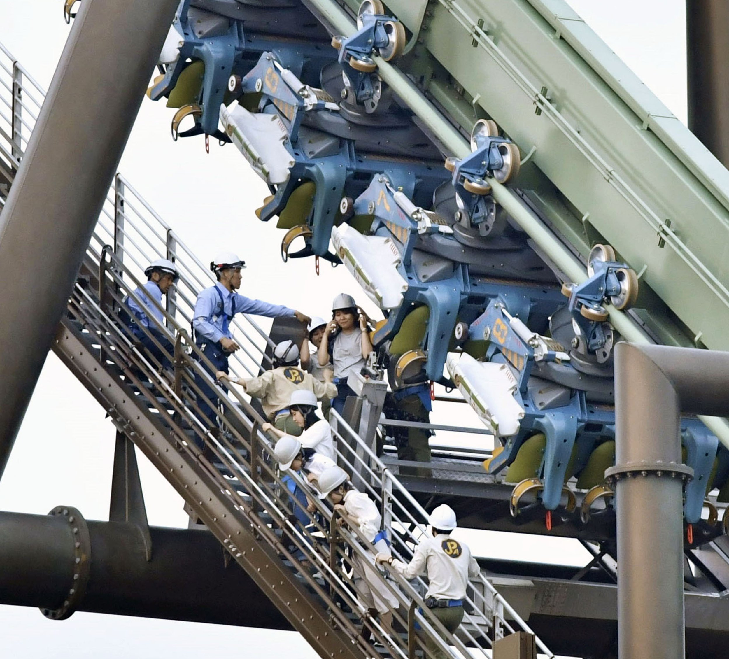 In this Tuesday, May 1, 2018, photo, passengers are rescued from the stopped Flying Dinosaur rollercoaster at Universal Studios Japan amusement park in Osaka, western Japan. Sixty-four passengers were left hanging in the air for up to two hours after the rollercoaster made an emergency stop. The amusement park said the rollercoaster's two carriages stalled midway through the 1,100-meter (yard) ride, with riders suspended in a flying position about 30 meters (100 feet) above the ground. (Chika Oshima/Kyodo News via AP)