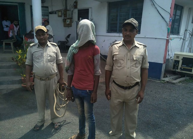 TOPSHOT - This photo taken on May 6, 2018 shows an alleged rapist (C) being held by Indian police, in the case of a 17-year-old girl who was raped and set on fire, at Mufasil police station before being sent to judicial custody in Pakur district, in India's eastern Jharkhand state. A 17-year-old battled for her life May 7 after being raped, doused in kerosene and set on fire, the second such case to shake India as it battles an increase in sexual crimes. / AFP PHOTO / --/AFP/Getty Images