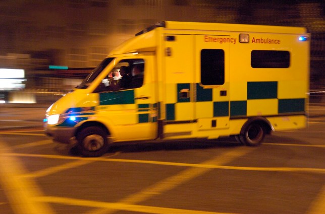 Large ambulance, emergency lights flashing, on road junction, King's Cross, London.