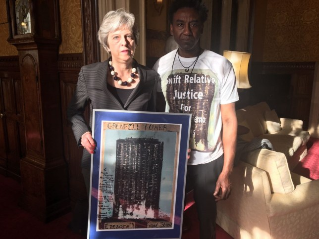 "Handout photo dated 10/05/18 issued by Relative Justice Humanity for Grenfell of Prime Minister Theresa May with artist Damel Carayol, who lost his niece in the Grenfell Tower fire. The print of ""Grenfell Tower: Eyesore!! Final Straw"", painted by Mr Carayol, is to be displayed in Downing Street after being presented at a meeting with survivors and families. PRESS ASSOCIATION Photo. Issue date: Friday May 11, 2018. See PA story POLITICS Grenfell. Photo credit should read: Relative Justice Humanity for Grenfell/PA Wire NOTE TO EDITORS: This handout photo may only be used in for editorial reporting purposes for the contemporaneous illustration of events, things or the people in the image or facts mentioned in the caption. Reuse of the picture may require further permission from the copyright holder."
