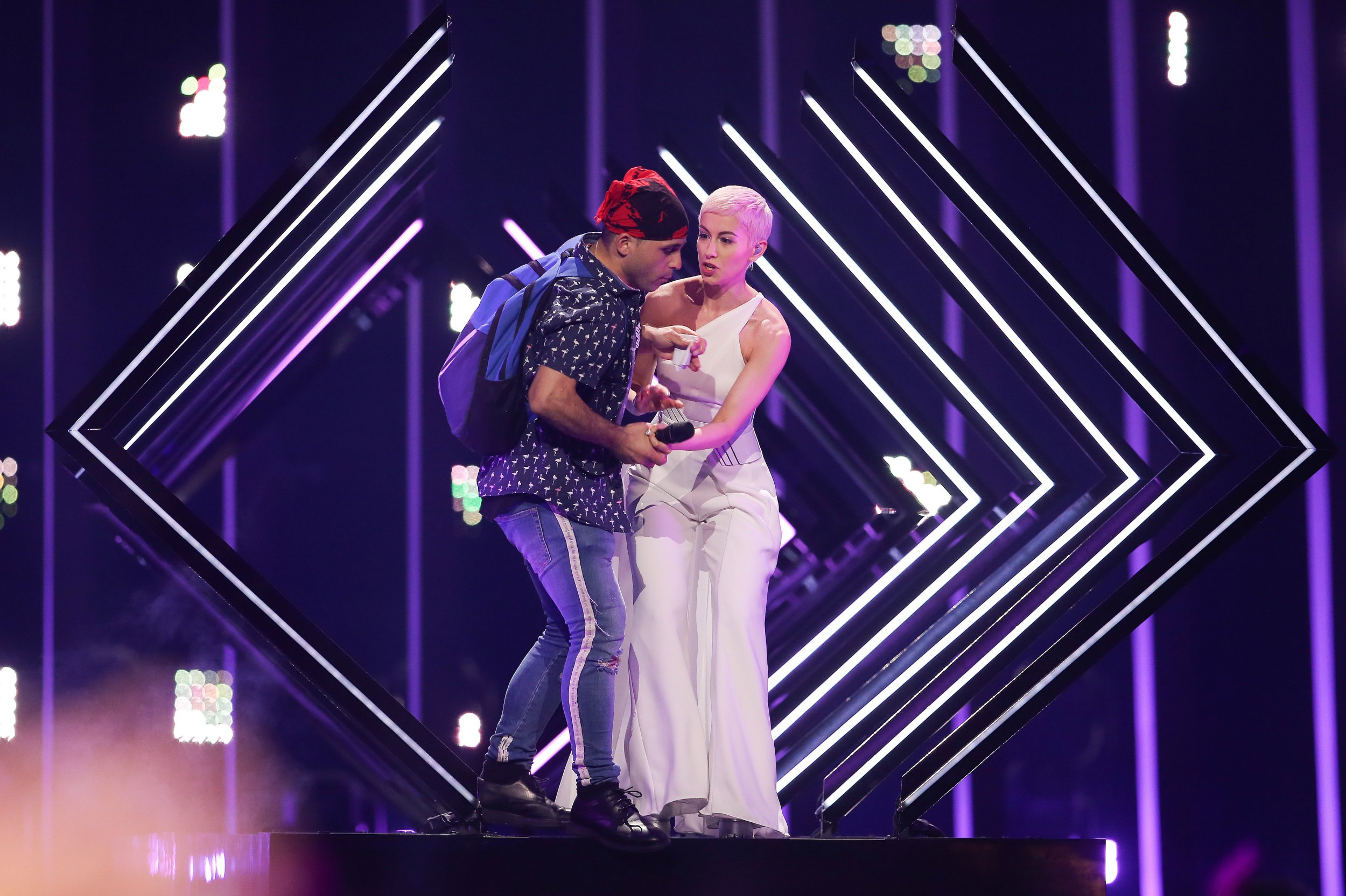 epa06731815 A fan invades the stage during the performance of SuRie (R) representing the United Kingdom with 'Storm' during the Grand Final of the 63rd annual Eurovision Song Contest (ESC) at the Altice Arena in Lisbon, Portugal, 12 May 2018. Twenty-six finalists are competing to win the ESC 2018. EPA/JOSE SENA GOULAO *** Local Caption *** 50359766
