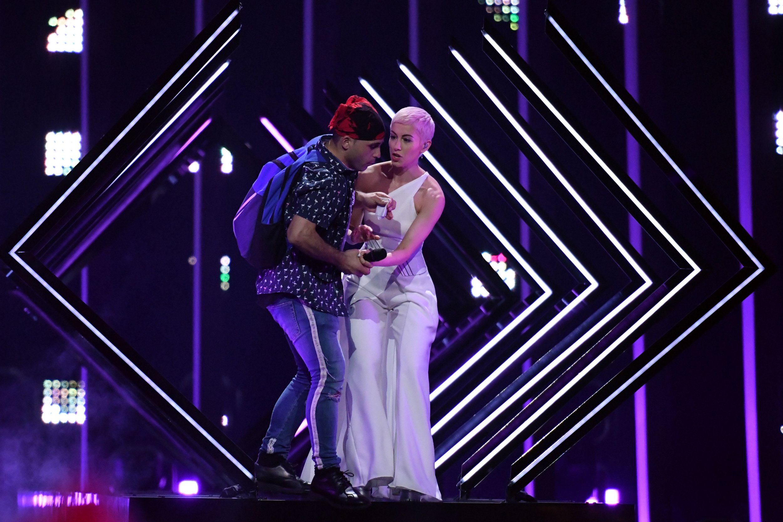 """A man takes the microphone from Britain's singer Susanna Marie Cork aka SuRie as she performs """"Storm"""" during the final of the 63rd edition of the Eurovision Song Contest 2018 at the Altice Arena in Lisbon, on May 12, 2018. / AFP PHOTO / Francisco LEONGFRANCISCO LEONG/AFP/Getty Images"""