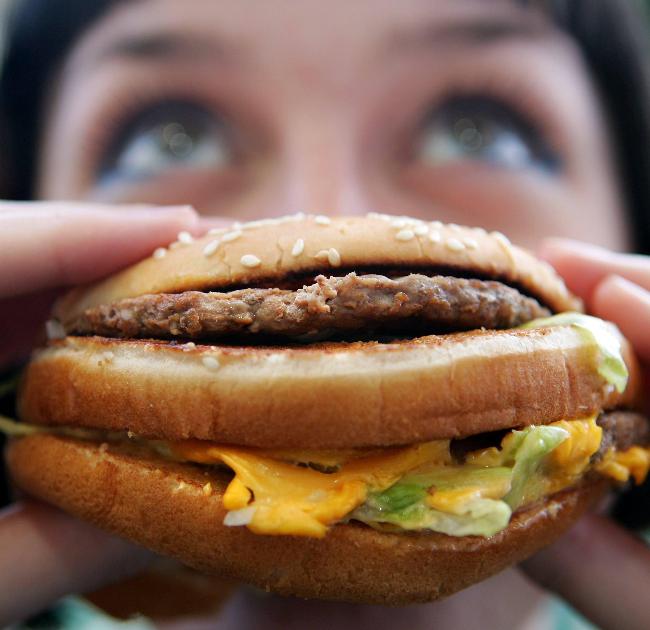 LONDON - JULY 12: In this photo illustration a lady eats a beefburger on July 12, 2007 in London, England. Government advisors are considering plans for a fat tax on foods high in fat to try to help tackle the fight against obesity. (Photo by Cate Gillon/Getty Images)
