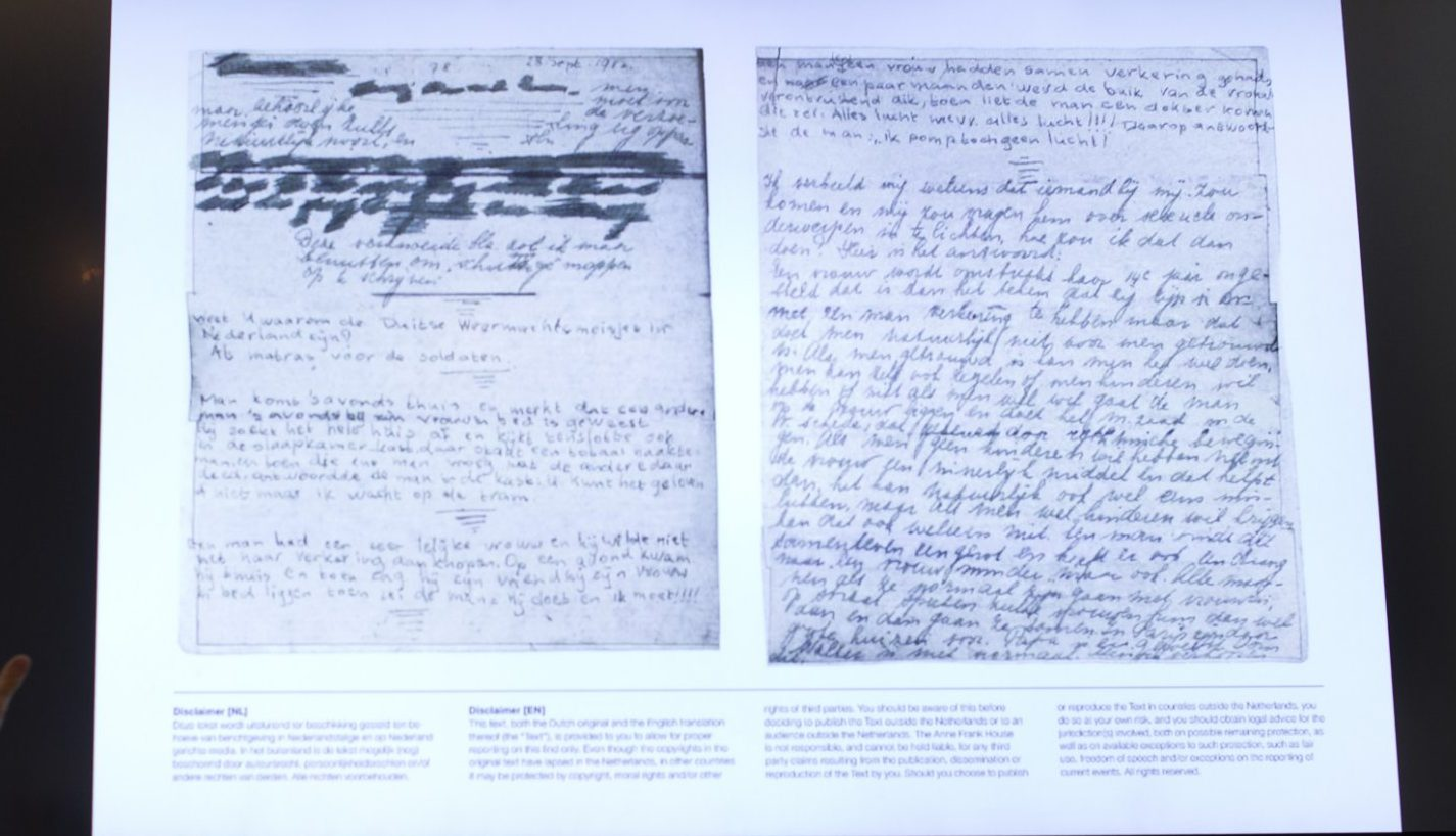 A video shows the text underneath two taped off pages from Anne Frank's diary during a press conference at The Anne Frank Foundation's office in Amsterdam, Netherlands, Tuesday, May 15, 2018. Left standing is the foundation's director Ronald Leopold. (AP Photo/Peter Dejong)