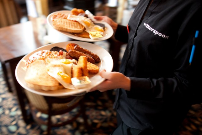 A bartender carries two breakfast plates at The Knights Templar public house Wetherspoon