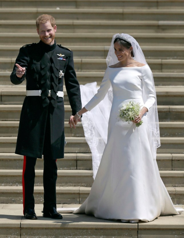 Meghan Markle and Britain's Prince Harry stand on the steps of St George's Chapel at Windsor Castle following their wedding in Windsor, near London, England, Saturday, May 19, 2018. (Jane Barlow/pool photo via AP)