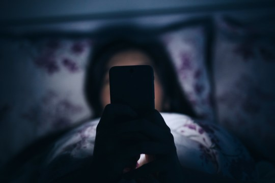 Woman texting and reading on smartphone in bed in midnight.