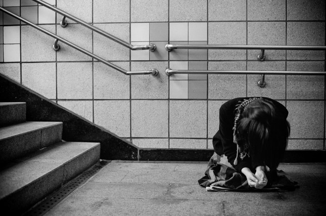 Woman Kneeling Against Wall At Underground Walkway