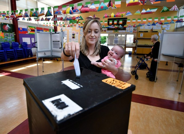 ATHLONE, IRELAND - MAY 25: Niamh Gavin casts her vote as she holds her daughter Fiadh aged 5 months at a polling station on May 25, 2018 in Athlone, Ireland. Voters in Ireland will decide whether to abolish or keep the 8th amendment which makes it illegal for a woman to have an abortion in the country unless in certain circumstances where her life is at risk. The result of the referendum is expected on Saturday. (Photo by Charles McQuillan/Getty Images) ***BESTPIX***