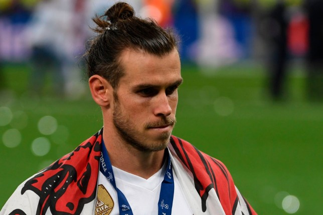 Real Madrid's Welsh forward Gareth Bale with his winner's medal and a Welsh flag on the pitch as Real Madrid players celebrate winning the UEFA Champions League final football match between Liverpool and Real Madrid at the Olympic Stadium in Kiev, Ukraine on May 26, 2018. Real Madrid defeated Liverpool 3-1. / AFP PHOTO / Paul ELLISPAUL ELLIS/AFP/Getty Images