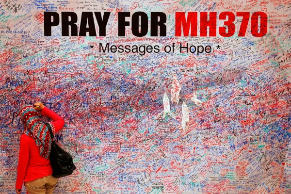 FILE PHOTO: A woman leaves a message of support and hope for the passengers of the missing Malaysia Airlines MH370 in central Kuala Lumpur March 16, 2014. REUTERS/Damir Sagolj/File Photo