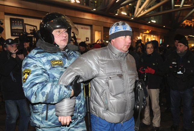 Russian riot police officers detain a protestor in central Moscow on December 15, 2010 during a demonstration for Yegor Sviridov, 28, a dedicated fan of the Spartak Moscow football team shot dead on December 4, 2010. Moscow police arrested more than 700 people Wednesday across the city centre in a bid to prevent ethnic clashes from erupting following the deadly shooting of a football fan, a spokesman said. AFP PHOTO/ ALEXANDER NEMENOV (Photo credit should read ALEXANDER NEMENOV/AFP/Getty Images)