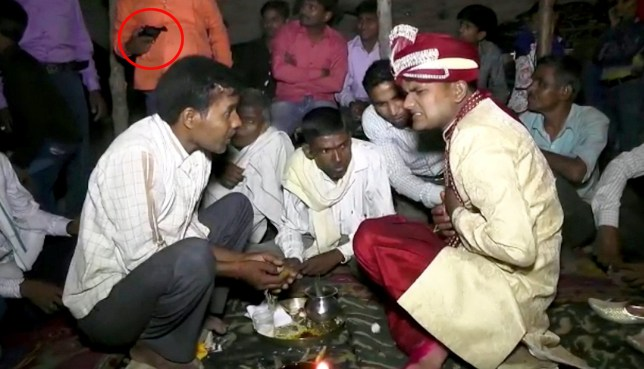 Police are hunting a gunman (orange shirt) accused of murder after he was captured on film shooting a groom in the chest during a wedding ceremony. See SWNS story SWGROOM. Newly-married Sunil Radayshyam Verma, 25, was sat in a circle surrounded by guests when he was struck in the chest. A video taken by the wedding photographer shows a man in orange clutching a gun, which goes off when he seemingly adjusts the top of the pistol. The groom looks around towards the shooter, before it fires for a second time, and he clutches his chest and falls forward. Police in in Uttar Pradesh?s Lakhimpur Kheri district in India are hunting for a man on suspicion of murder.